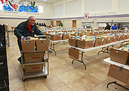 Mike Guge of Solon moves a cartload of food boxes out to a truck as the Society of St. Vincent de Paul delivers 237 holiday meals to families in Cedar Rapids, Marion, and Hiawatha from the St. Wenceslaus Church gym at 1230 5th St SE in Cedar Rapids on Saturday morning, December 22, 2012. (Stephen Mally/Freelance)