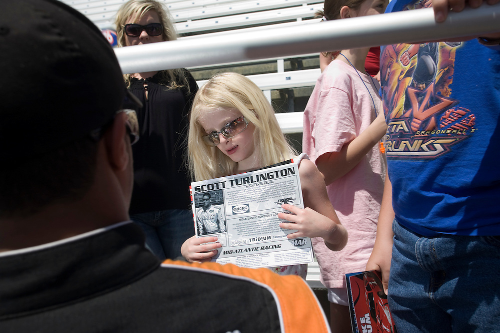 A young racing fan receives autographed glossy photographs from ARCA/REMAX series drivers at Rockingham Speedway.
