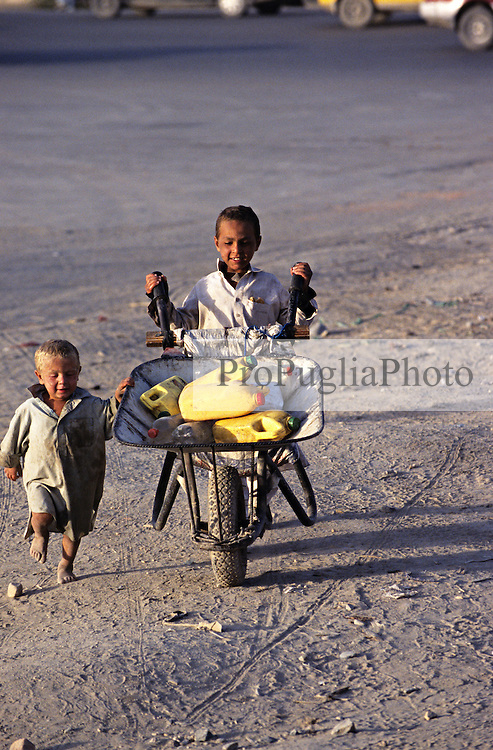 A boy proudly push his load of water and the youngest  joins up the efforts!