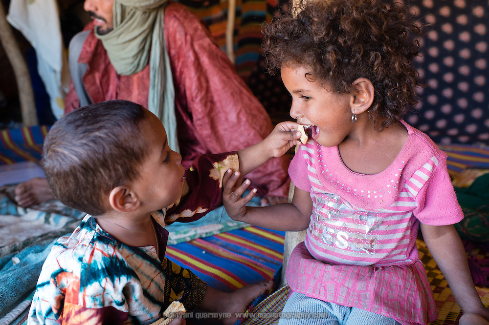 Mohammed Ould Mine's children sharing a biscuit in the family's tent at the Mbera refugee camp in southeastern Mauritania on 1 March 2013.
