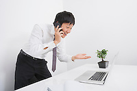 Surprise businessman using cell phone and laptop in office