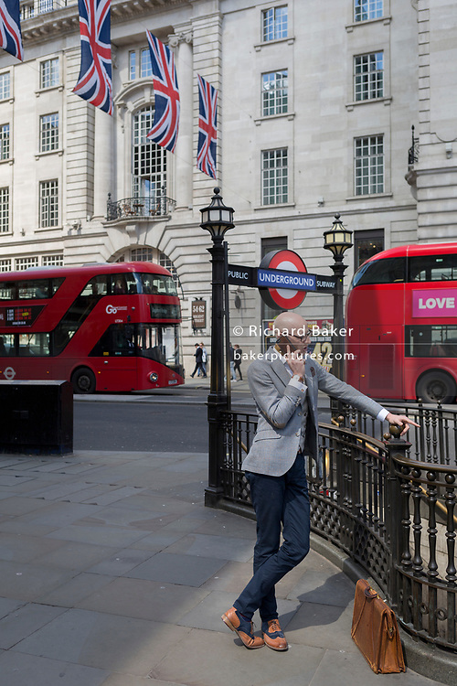 A well-dressed young man talks on his phone while leaning on railings at a Piccadilly Circus underground station entrance  on 1st May, in London, England.