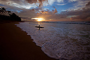 A surfer heads into the surf as the sun sets on Oahu's world famous north shore, Hawaii