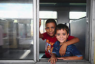 """Boys in train station, waiting for the """"toy train"""" (a small narrow-gauge train) to leave to Shimla"""