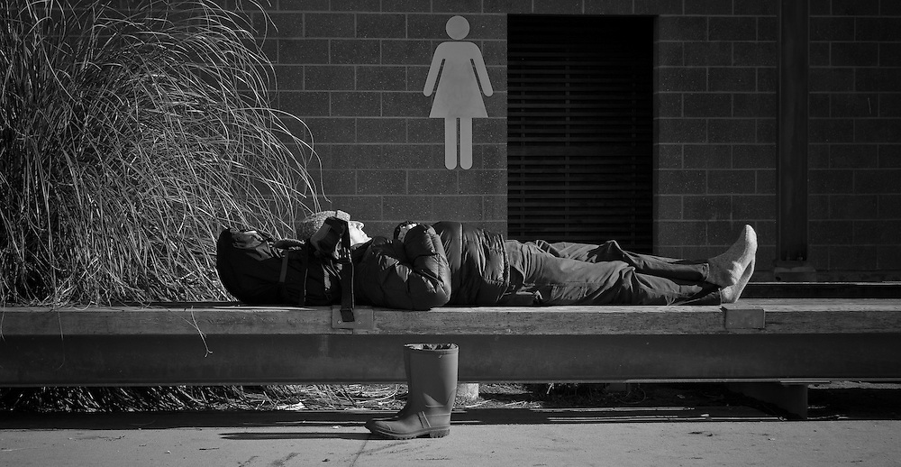 A man relaxes under the midday sun in a park in Vancouver.