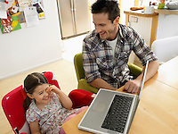 Girl (3-6) using laptop with father in kitchen