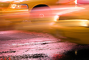 Yellow taxi cabs speed through Times Square on a rainy night in Manhattan, New York City.