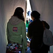 Two American University students, Christina and Lina, peek through the side of a tent at the stage for the Rally to Restore Sanity and/or Fear on the National Mall in Washington, D.C. on Saturday, October 30th, 2010...(Samuel Corum for TBD)
