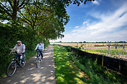 Fietsers rijden op het fietspad door de weilanden tussen Steenwijk en Meppel.<br /> Cyclists ride at the bike lane between Steenwijk and Meppel.