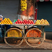 India. Bihar. Bodhgaya, the town where the Buddha sat under a sacred fig tree (bhodi tree) and received enlightenment. Fruit cart selling satsumas, pomegranates and apples