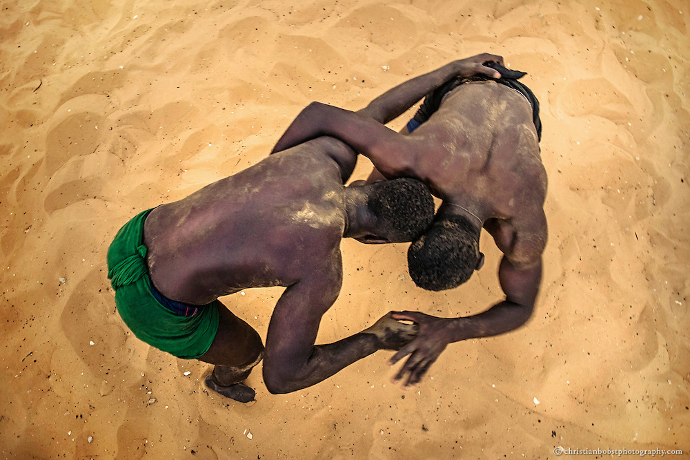 Two wrestlers train at a wrestling school on April 7, 2015. The Senegalese wrestling match always takes place in the sand. The fighters try to pack each other on the legs, to unbalance the opponent, what leads to similar positions and movement patterns like wrestling matches in other countries.