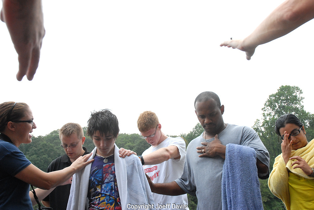 I took this picture Sunday morning as I was heading for a walk with my friend on a trail near the Chattahoochee River. A group of people was gathered by the bank of the river. As we got closer we saw people being dipped into the river and then pulled out. They were being baptized. At the edge of the river people gathered around the individuals who had been baptized, talking about them and praying over them. <br /> <br /> Joseph Harmon (center) was one of the people who had been baptized. Joseph is 14 years old and in eighth grader. &quot;At that moment,&quot; he explained to me after looking at this picture, &quot;it felt like everybody was concentrating on me and praying for me. It felt kind of awkward, just how everyone was praying over me. I didn't know what to think. It was kind of breath taking.&quot;