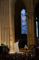 Our Lady of Chartres Cathedral, Chartres, France. Priest raising a hand to a stained glass window. In the background is a beautiful blue window and impressive stone arches.