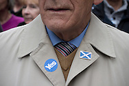 An elderly man with a 'Yes' sticker and badge on his coat waiting on the Royal Mile for the start of a pro-Independence march and rally in the Scottish capital. The event, which was staged in support of the pro-Independence movement, was attended by an estimated by approximately 30,000 people. The referendum to decide whether Scotland will become an independent nation will be staged on 18th September 2014.
