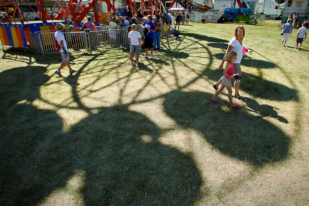 Jonni Horton and her daughter Cooper Horton, 6, walk beneath the ferris wheel on the midway of the North Idaho Fair on opening day Wednesday.