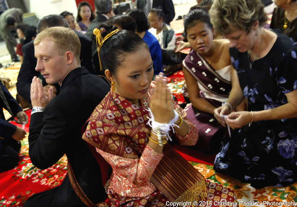 Vee Somphanith in her a traditional Laotian wedding dress and Jesse Wojtkiewicz are gathered around by family and friends who wrapped yarn around their wrists to wish them well during a baci ceremony performed at Laotian weddings.  Wojtkiewiecz's mother, Eveyln, right, prepares to put a wish for the couple.