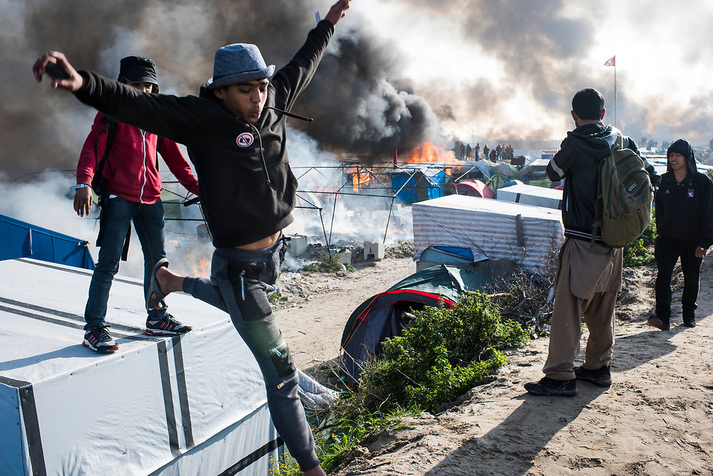 As The Jungle refugee camp burns, a refugee leaps from the roof of a residence to the berm that delineates the edge of camp on October 26, 2016 in Calais, France.
