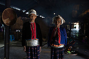 Two old women who are member's of a sub-group of the Palaung ethnic minority stands inside her family's communal house. The tribe is famous for the silver bands un-married girls wear around their waist, the number depending on the wealth of their family. Once they are married most are removed leaving only a few remaining.