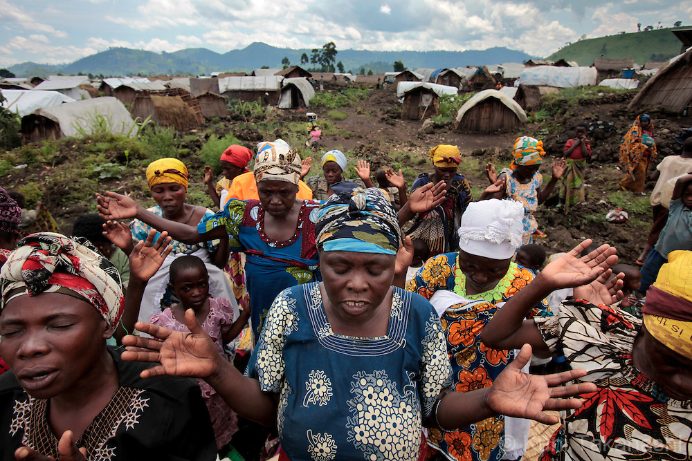 Women pray during church service at Mungote camp for IDPs (Internally Displaced Persons) in Kichanga, 70km north of Goma, DRC on April 25, 2010. The camp was established in Jan 2008 and has population of 95,000. .Photo by Kuni Takahashi.