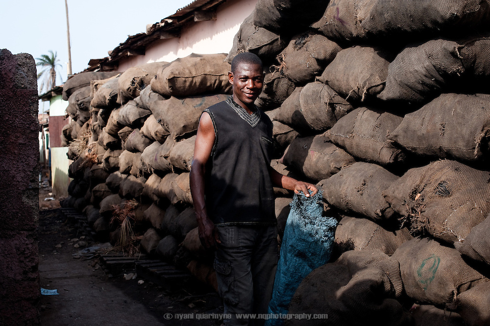 Saeed Tamimu buying charcoal in Nima, a densely populated area of Accra, Ghana. He buys two bags a day for GHC1.60/ bag, receiving a 0.10 discount as he has been a customer for sven years. The charcoal is used for cooking - he has a family business selling local food - and some is onsold.