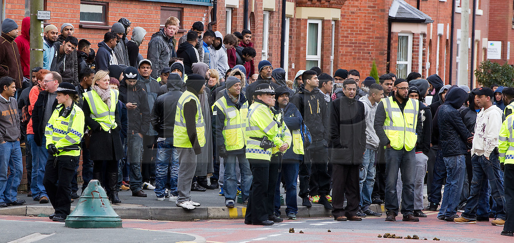 © licensed to London News Pictures. Hyde, UK  25/02/2012. The EDL demonstrate following an assault on Daniel Stringer-Prince. Asian men gather outside the town's larger mosque. The victim's family said they did not want the EDL to demonstrate in their town in their son's name. It is alleged he was assulted by a gang of Asian men. At the same time, the BNP hold a rally in the town. Photo credit should read Joel Goodman/LNP