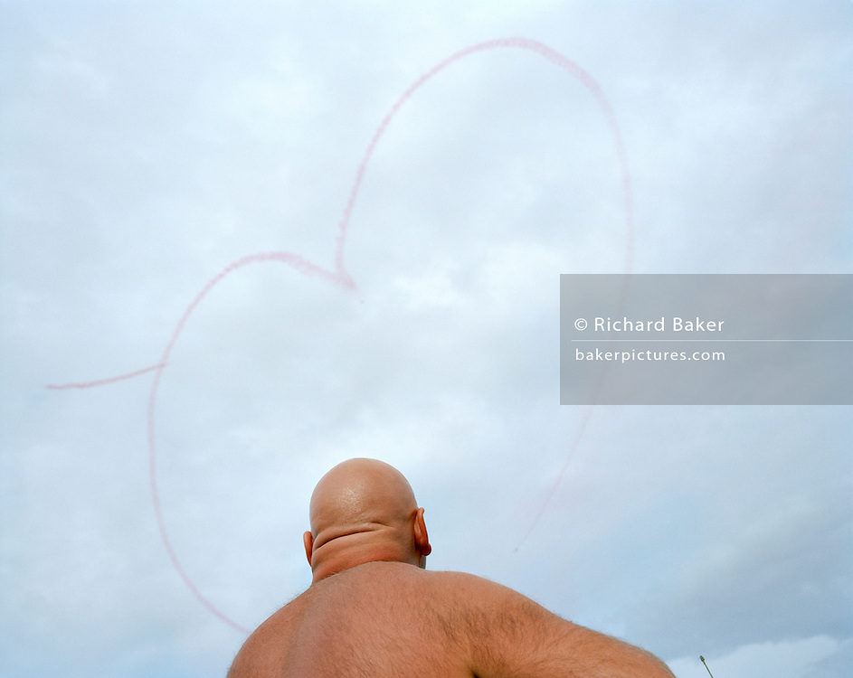 A large man with a shaved head and hairy back is seen from behind as he watches a display by the elite 'Red Arrows', Britain's prestigious Royal Air Force aerobatic team at Weymouth, England. A heart shape which grows from his bald head has been drawn with red smoke in the sky two Hawk jet aircraft taking part in the town's annual air show along the sea front. Such a tough-looking male specimen contrasts with the romance of this valentine symbol helping to make this picture's quirky juxtaposition touching. The Red Arrows use smoke to emphasize their flight-path, help the spectators see their manoeuvres and to make more of an enjoying spectacle. In blue sky they use white smoke for The Heart and red when overcast. We watch the man from below and see him craning his neck skywards, the skin on his thick neck wrinkling as he looks heavy from this angle.
