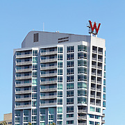The W Hotel rising above the treetops of a waterfront park in Hoboken, New Jersey. The hotel offers views of the New York City Skyline directly opposite on the Hudson River. Hoboken, New Jersey, USA