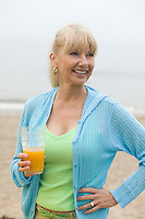 Mid-adult woman on beach holding a glass of orange juice