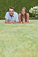 Portrait of smiling young couple lying side by side on grass in park