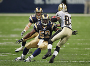 ST. LOUIS - SEPTEMBER 23:  Wide receiver Donte' Stallworth #83 of the New Orleans Saints avoids a tackle by safety Adam Archuleta #31 and linebacker Dexter Coakley #52 of the St. Louis Rams at the Edward Jones Dome on September 23, 2005 in St. Louis, Missouri. The Rams defeated the Saints 28-17. ©Paul Anthony Spinelli *** Local Caption *** Donte' Stallworth;Adam Archuleta;Dexter Coakley