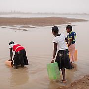 Rihanata Ouedraogo (15, centre) and her sisters, Alimata (18, right) and Nafisatou (17) collecting untreated water from a dam in Koala, Burkina Faso on 1 March 2014.