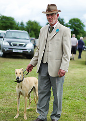 © Licensed to London News Pictures.29/07/15<br /> Borrowby, UK. <br /> <br /> A steward stands with his whippet at the Borrowby Country Show and Gymkhana in North Yorkshire.<br /> <br /> Photo credit : Ian Forsyth/LNP