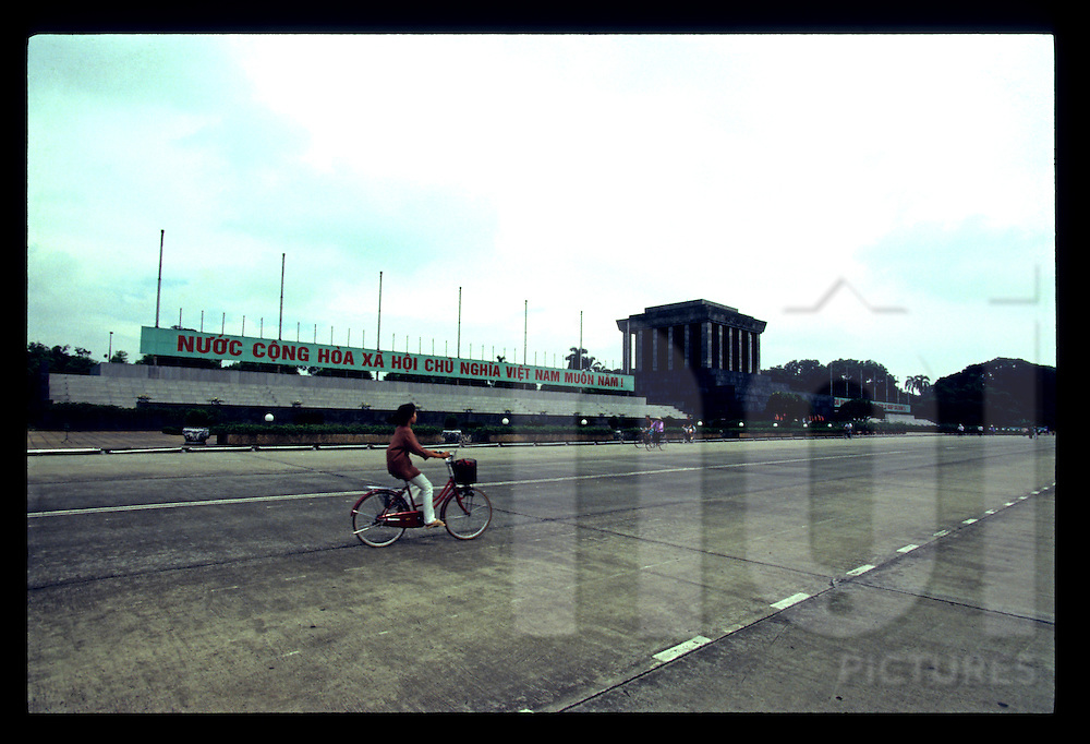 A young vietnamese girl rides her bicycle along Ho Chi Minh Mausoleum, Hanoi, Vietnam, Southeast Asia, 1997
