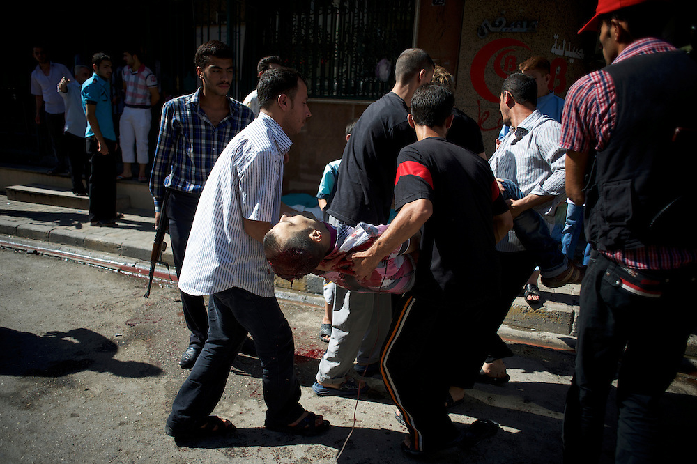 August 10, 2012 - Aleppo, Syria: A group of men carry the dead body of a man killed minutes earlier by heavy shelling from the Syrian Army against a bakery in the residential area of Tariq Al-Bab in central Aleppo. At least 12 people have died and more the 20 got injured during the attack...The Syrian Army have in the past week increased their attacks on residential neighborhoods where Free Syria Army rebel fights have their positions in Syria's commercial capital, Aleppo.