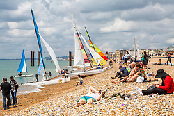 © Licensed to London News Pictures. 14/07/2019. Brighton, UK. Visitors watch the sailing boats return to Brighton and Hove beach after a morning out on the sea. Photo credit: Hugo Michiels/LNP