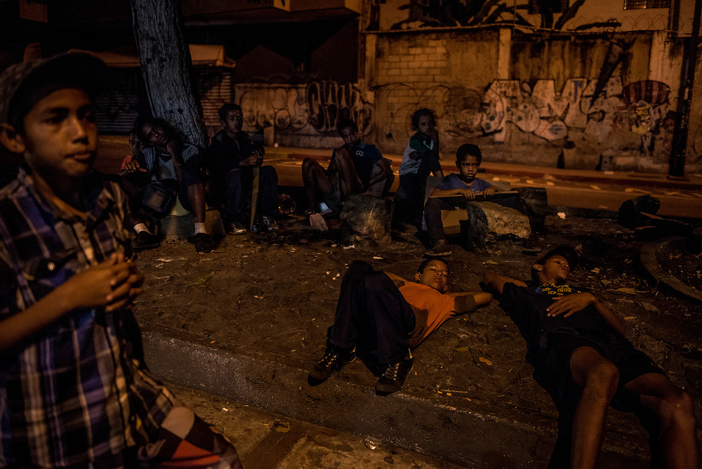 CARACAS, VENEZUELA - OCTOBER 17, 2017:  Members of a street gang of young boys wait for employees of a large shopping center to take the day's trash out to the outside dumpster, so that the boys can scavenge in it for discarded food and recyclables. A growing number of young boys  are leaving their homes outside of the city to live in the streets of Caracas where it is easier for them to attain food. They join street gangs with other homeless youth, and engage in knife fights in order to expand and defend their territories and control over sought after areas for panhandling and picking through garbage. Several young gang members interviewed by The New York Times said they prefer to live in the streets, despite the danger - because they eat better than they could living at home with their families. PHOTO: Meridith Kohut for The New York Times