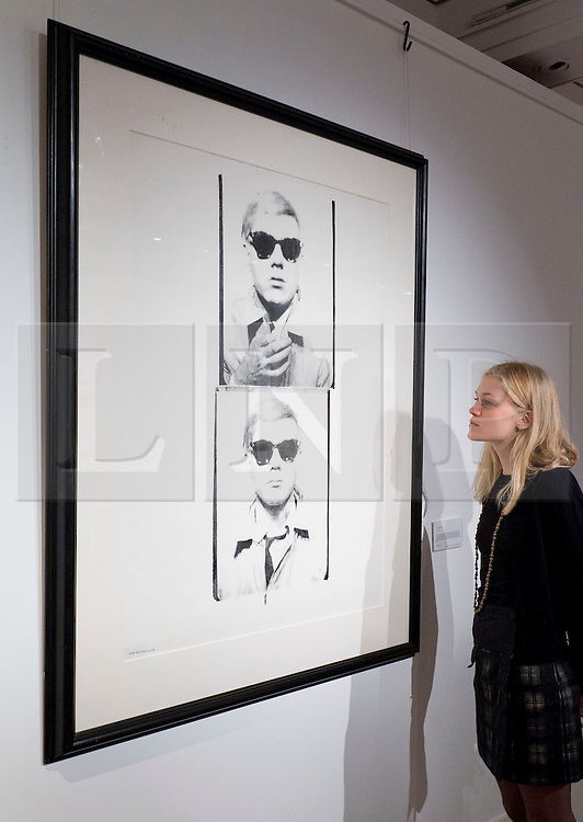 © Licensed to London News Pictures. 13/09/2013. London, UK. A Sotheby's employee views 'Self Portrait' (circa 1978) (est. GB£60,000-80,000), a unique screenprint by Andy Warhol, at the press view for Sotheby's 'Prints and Multiples Sale' on New Bond Street in London today (13/09/2013). The auction, set to take place on the 17th of September, includes works by Munch, Rembrandt, Basquiat, Warhol and Picasso. Photo credit: Matt Cetti-Roberts/LNP