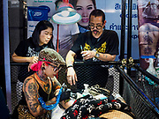 28 OCTOBER 2018 - BANGKOK, THAILAND: A woman checks her smart phone while she gets a tattoo at the 2018 MBK Center Tattoo Fest. Tatoo artists from around the world came to participate in the festival, which featured both modern (using tattoo machines) and traditional methods (done by hand with long needles) of tattooing.      PHOTO BY JACK KURTZ