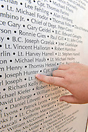 """East Meadow, New York, U.S. 11th September 2013. ROSEMARY HUNTER, of Wantagh, points her finger to name of her brother-in-law, Joseph G Hunter, during her visit to the Global War on Terror """"Wall of Remembrance"""" a traveling memorial on display in New York for the first time, at Eisenhower Park on the 12th Anniversary of the terrorist attacks of 9/11. Joseph Hunter was a firefighter, in Squad 288 in Maspeth Queens, who died September 11, 2001. The unique 94 feet long by 6 feet high wall has, on one side, almost 11,000 names of those lost on September 11th 2001, along with heroes and veterans who lost their lives defending freedom of Americans over past 30 years."""