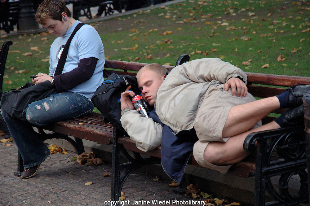 Young lad after on bench after night of boozing.