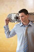Young Businessman Holding Skateboard
