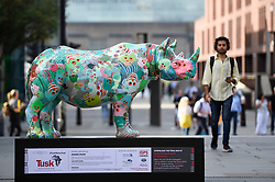 "**CAPTION CORRECTION - Rhino statues are 750mm tall, not 750cm tall, as stated in previous captions**<br /> © Licensed to London News Pictures. 20/08/2018. LONDON, UK. A man passes by ""The Poppy Rhino"", a rhino painted by Zhang Huan, near the Millennium Bridge.  At 750mm tall and weighing 300 kg, each rhino has been specially embellished by an internationally renowned artist.  21 rhinos are in place at a popular location in central London, forming the Tusk Rhino Trail, until World Rhino Day on 22 September to raise awareness of the severe threat of poaching to the species' survival.  They will then be auctioned by Christie's on 9 October to raise funds for the Tusk animal conservation charity.  Photo credit: Stephen Chung/LNP"