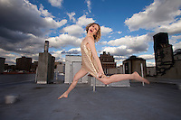 Woman in gold on Rooftop. Sexy 30's woman jumps for joy on an urban rooftop.