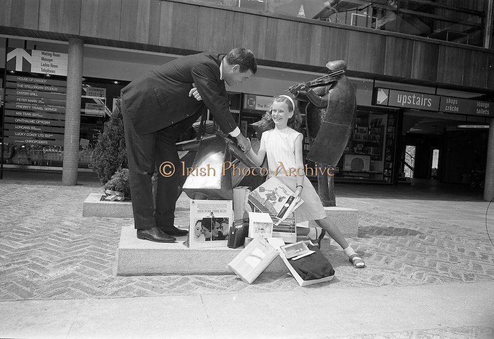 """17/07/1967<br /> 07/17/1967<br /> 17 July 1967<br /> Window spotting competition winner at Stillorgan Shopping Centre, Dublin. Eleven year old Elaine, daughter of Mr and Mrs William Stapleton of 45, Dole Road, Stillorgan, won the Stilorgan Shopping Centre Window Spotting Competition from nearly 1,000 entrants in """"spot the deliberate mistake"""" competition at the centre. Picture shows Mr Douglas Bain, Chairman of the Stillorgan Shopping Centre Merchants Association presenting the prizes to Elaine."""