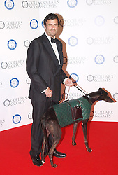 Designer Trevor Pickett with Willow, the 6 year old labrador wearing his designer coat, collar and lead designed by Vivienne Westwood at  the Collars & Coats Gala ball, the Battersea Dogs Home, November 8, 2012. Photo by i-Images.
