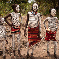 Children from the Karo tribe cover in full body paint.