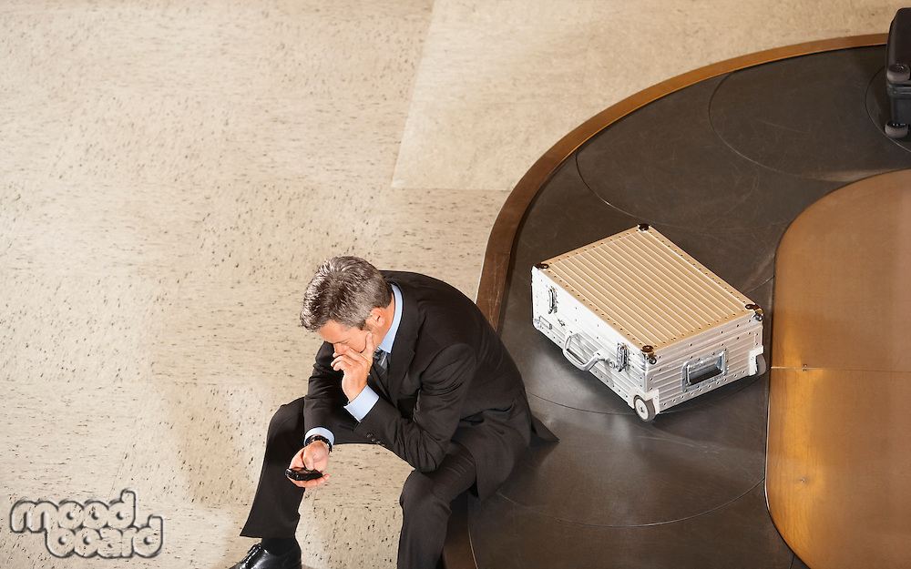 Business man looking at mobile phone sitting on luggage carousel in airport