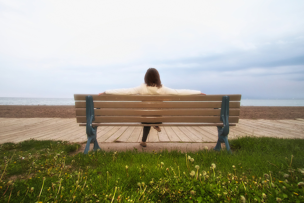 Woman sitting on bench overlooking the boardwalk, beach and Lake Ontario (Toronto, Canada)