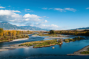 Anglers fly fish for trout from a drift boat during an autumn day on the South Fork of the Snake River, Idaho.