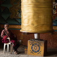 Man sits with the prayer wheel in the entry to the Punakha Dzong, Punakha, Bhutan